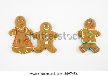 Frowning male gingerbread cookie standing separate from happy gingerbread cookies holding hands.