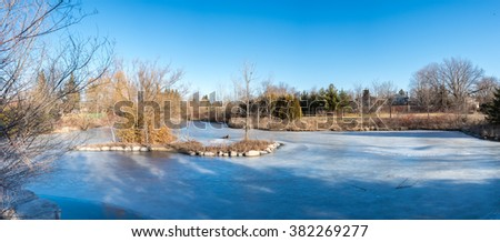 Frozen lake, in the middle of winter time, due to low temperatures the trees along side the like lack leaves and and vegetation