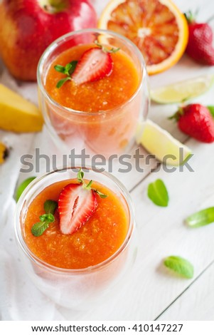 Fruit shakes with ingredients (apple, banana, lome, strawberry, orange, mint) on white wooden table. Healthy breakfast concept