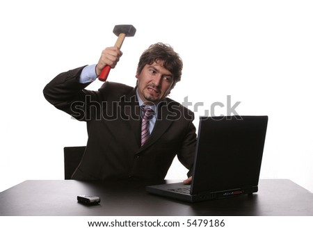 Frustrated businessman in his office threatening to destroy his PC with a hammer out of sheer frustration