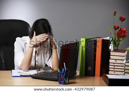 Frustrated young businesswoman analyzing chart during overtime