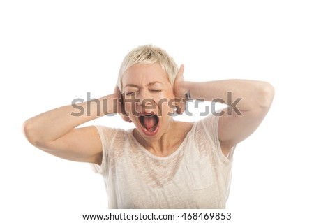 Frustrated young woman holding hands on ears, keeping eyes closed and cry.