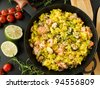 Frying pan with seafood paella and herbs. Viewed from above. - stock photo