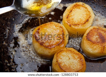Frying potato slices in a pan browning.