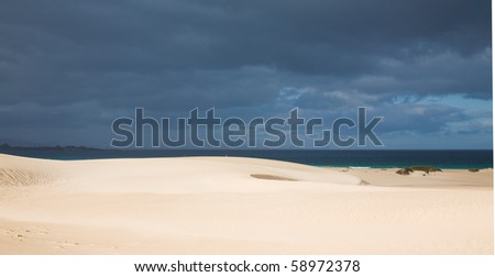 Fuerteventura; Corralejo sand dunes nature park; sand dunes in the sun; overcast ocean and Lanzarote in the background;