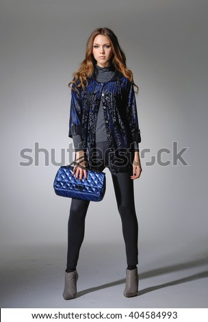 Full body fashion model with handbag posing in studio