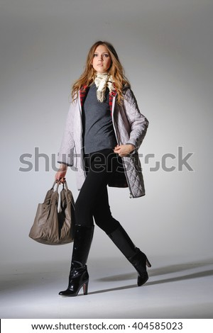 Full body Fashion photo of young sensual woman holding bag walking in studio