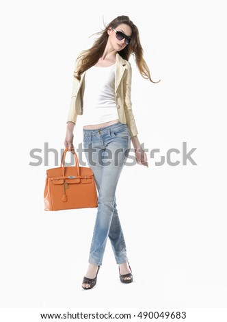 Full body Fashion portrait of beautiful young woman Girl in sunglasses and jeans. Girl with handbag