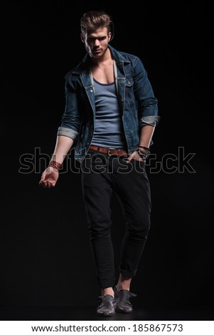 full body picture of a fashion man in a sexy pose on dark studio background