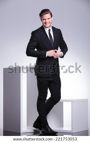 Full body picture of an attractive business man closing his jacket while smiling for the camera.