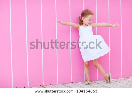 Full body portrait of adorable little girl outdoors against colorful wall