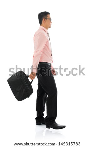 Full body side view young Asian businessman walking with briefcase, isolated on white background