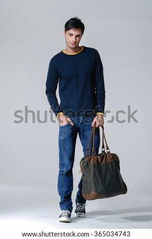 Full body young Casual man walking holding a bag over isolated