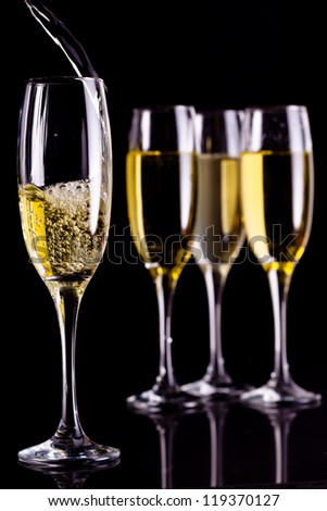 Full glasses of champagne and one being filled against black background