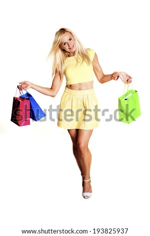 Full length front view of young woman walking with shopping bags over white background. Woman shopping.