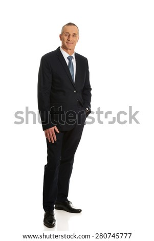 Full length mature businessman with hand in pocket.