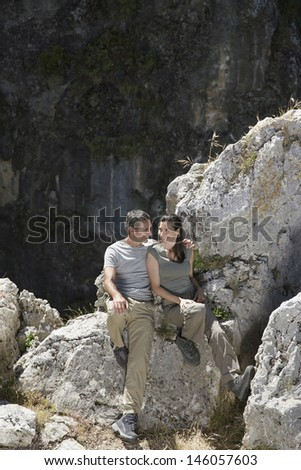 Full length of a relaxed smiling couple sitting on rocks