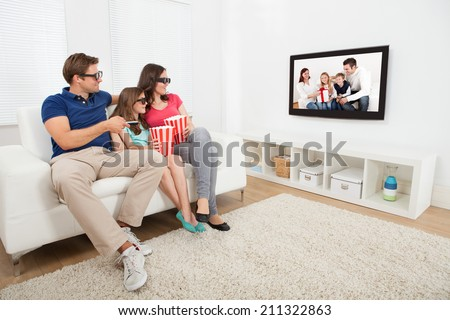 Full length of family watching 3D movie on television while having popcorn at home