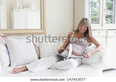 Full length of happy young pregnant woman using laptop in living room