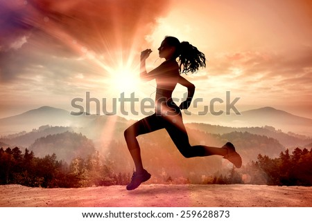 Full length of healthy woman jogging against misty landscape