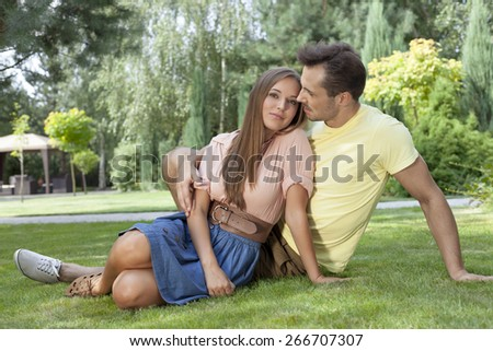 Full length of romantic young couple relaxing on grass in park