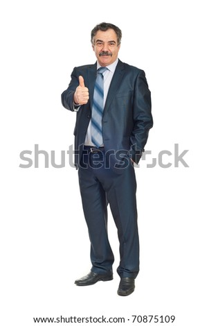 Full length of smiling senior business man giving thumb up and holding a hand into suit pocket isolated on white background