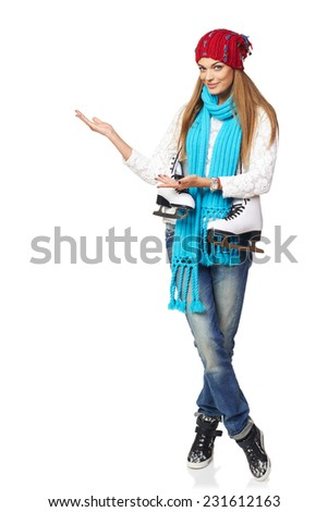 Full length of smiling young woman carrying a pair of ice skates inviting you to skating-rink, over white background