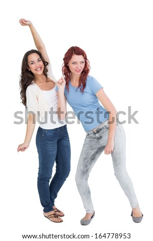 Full length of two cheerful young female friends dancing over white background