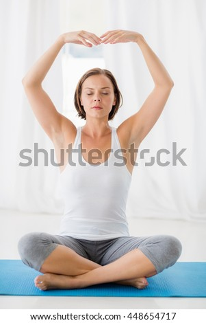 Full length of woman with eyes closed doing yoga at fitness studio