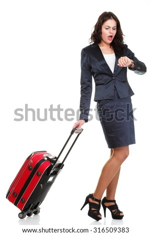 Full length of young business woman to late pulling red travel bag isolated on white background