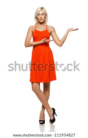 Full length of young trendy woman in bright red dress showing a product - empty copy space on the open hand palm, over white background