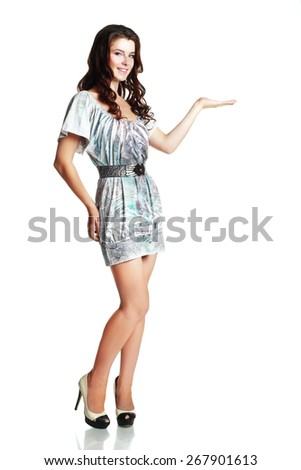 Full length of young trendy woman in summer dress showing a product - empty copy space on the open hand palm, over white background