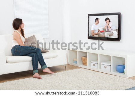 Full length of young woman watching television while sitting on sofa at home