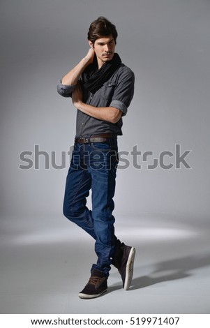 full length photo of a young casual man in jeans posing-light background