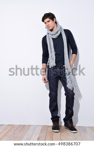 full length photo of a young casual man with,scarf posing.on wooden background