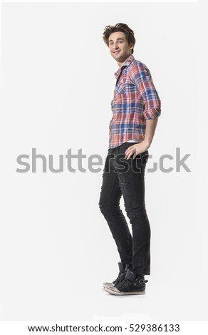 Full length portrait of a casual man in jeans posing over white background