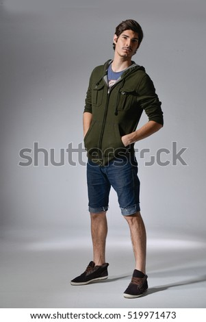 Full length portrait of a casual man in short jeans posing over gray background