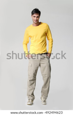 Full length portrait of a casual man posing over gray background