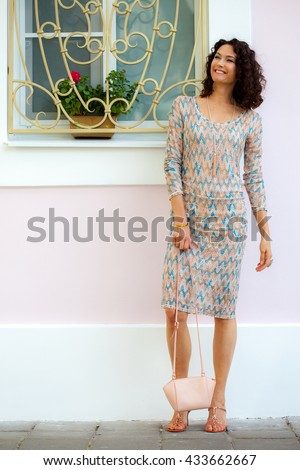 Full length portrait of a laughing beautiful middle-aged woman outdoors. fashion
