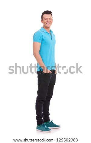 Full length portrait of a stylish young man standing with hands in pockets and looking at the camera over white background