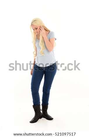 full length portrait of a woman with long blonde hair wearing casual blue shirt and jeans. standing pose. isolated on a white background.