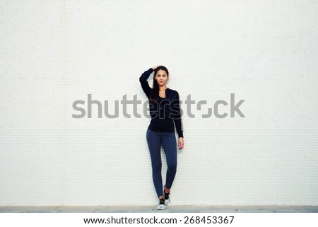 Full length portrait of an attractive and sporty young woman standing against a white background while getting ready for workout outdoors, cross process, filtered image