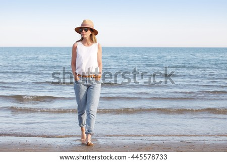 Full length portrait of an attractive mature woman walking on the beach barefoot. Beautiful female in straw hat and sunglasses wearing casual clothes.