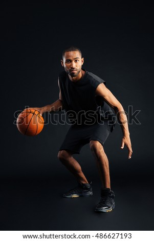 Full length portrait of an concentrated african man playing basketball isolated on a black background