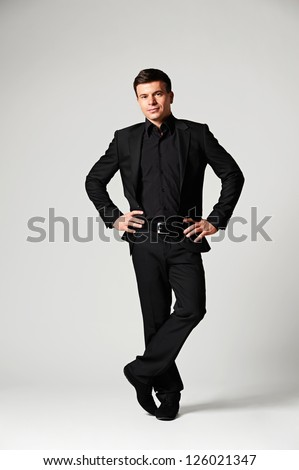 full length portrait of assured stylish businessman over grey background