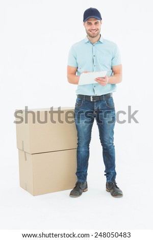 Full length portrait of happy delivery man writing on clipboard over white background