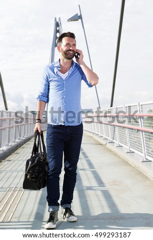 Full length portrait of happy mature man walking on bridge and using mobile phone