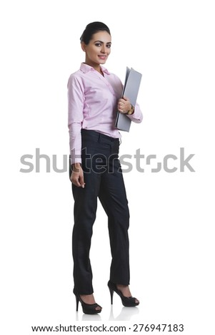 Full length portrait of Indian businesswoman holding file folder over white background