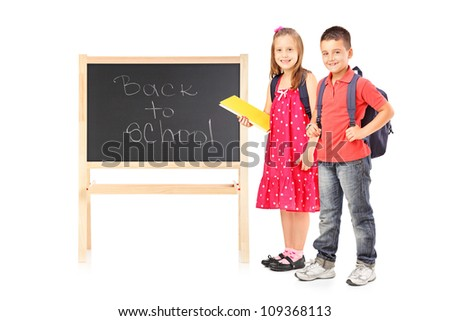 Full length portrait of schoolgirl and boy posing next to a board isolated on white background