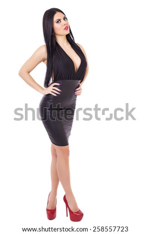 Full length portrait of sexy young brunette woman wearing a black dress and red shoes against white  background